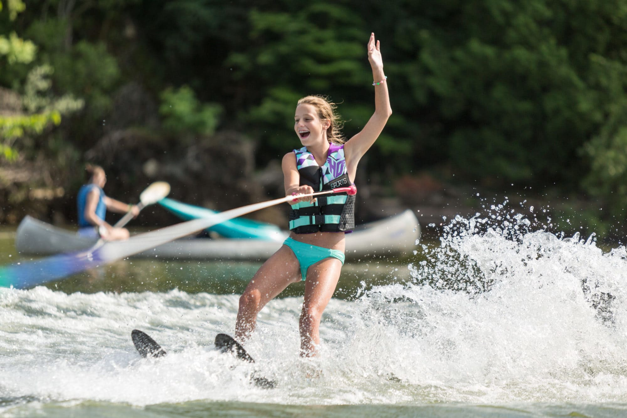 Girl waterskiing with one hand